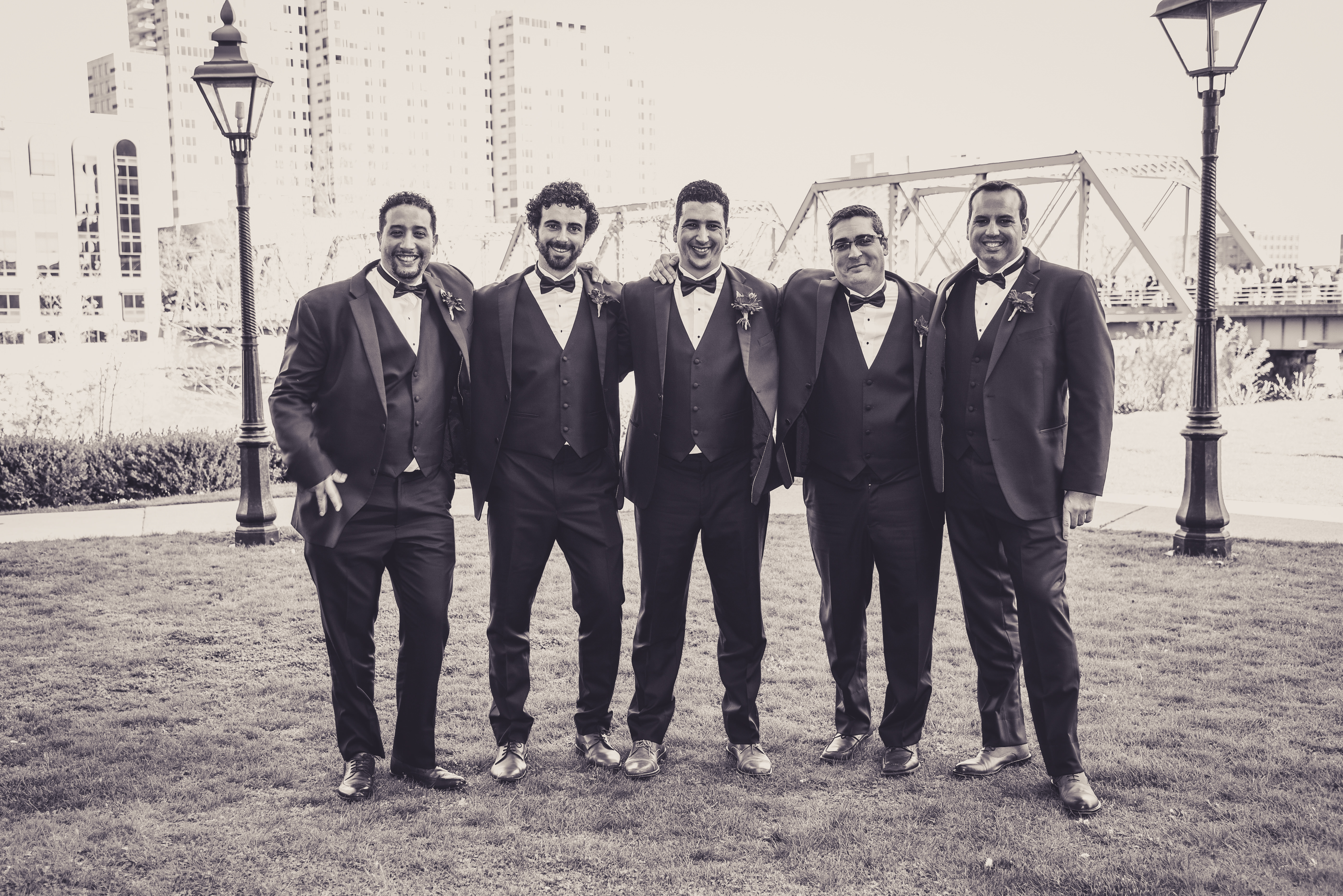 groomsmen in front of a bridge