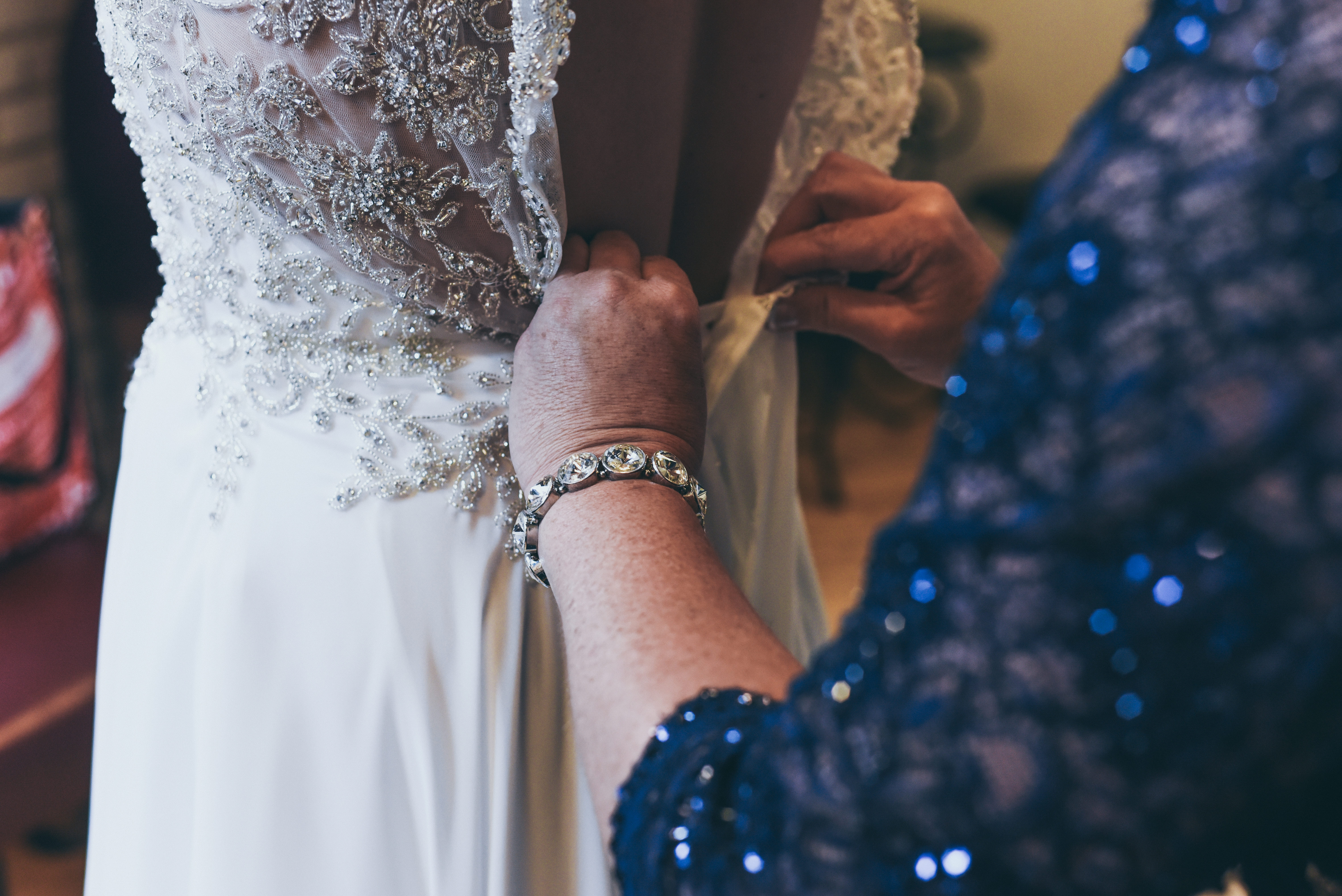 close up of mother's hands as she fastens her daughters wedding gown