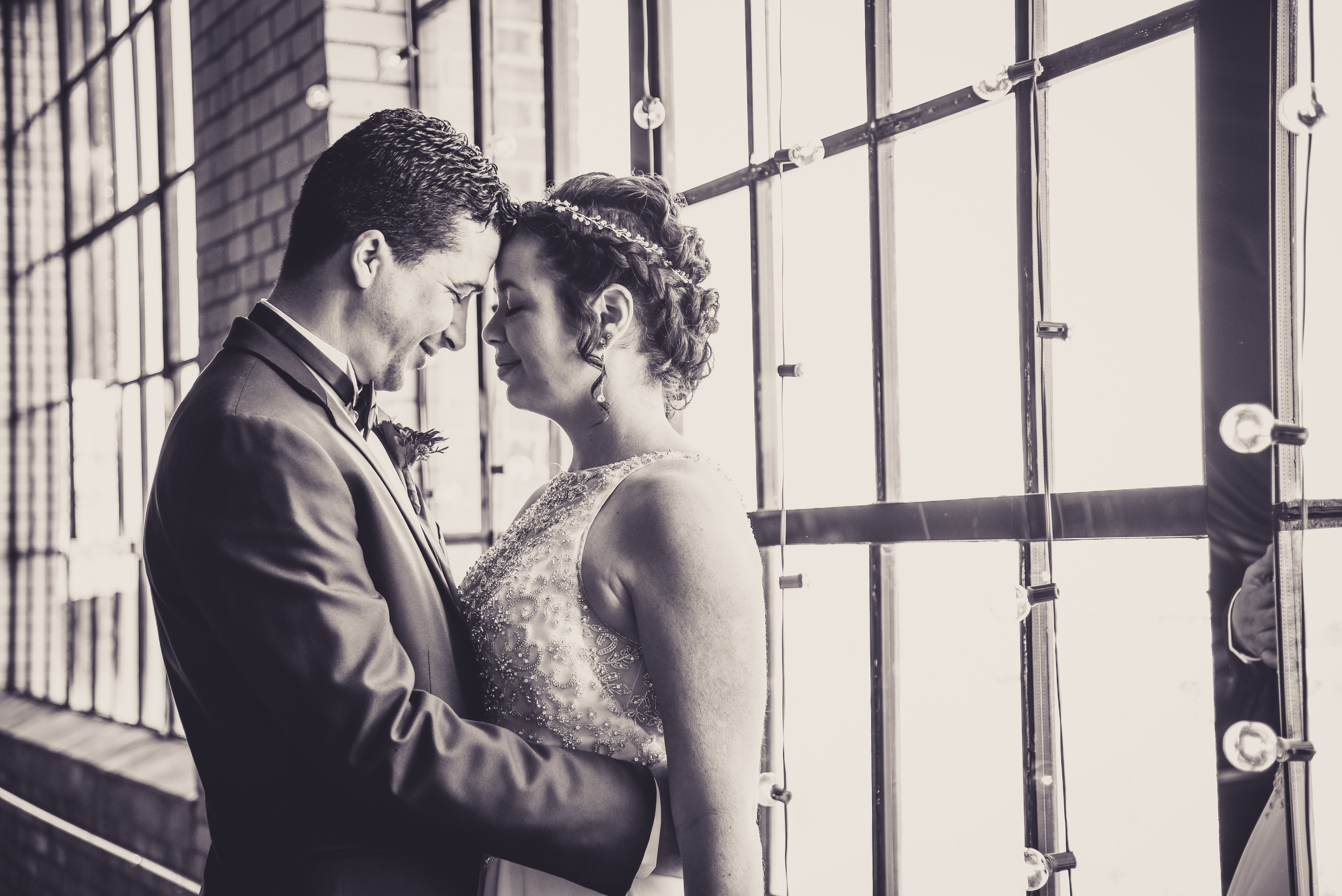 a photo of a bride and groom kissing in an industrial loft wedding venue