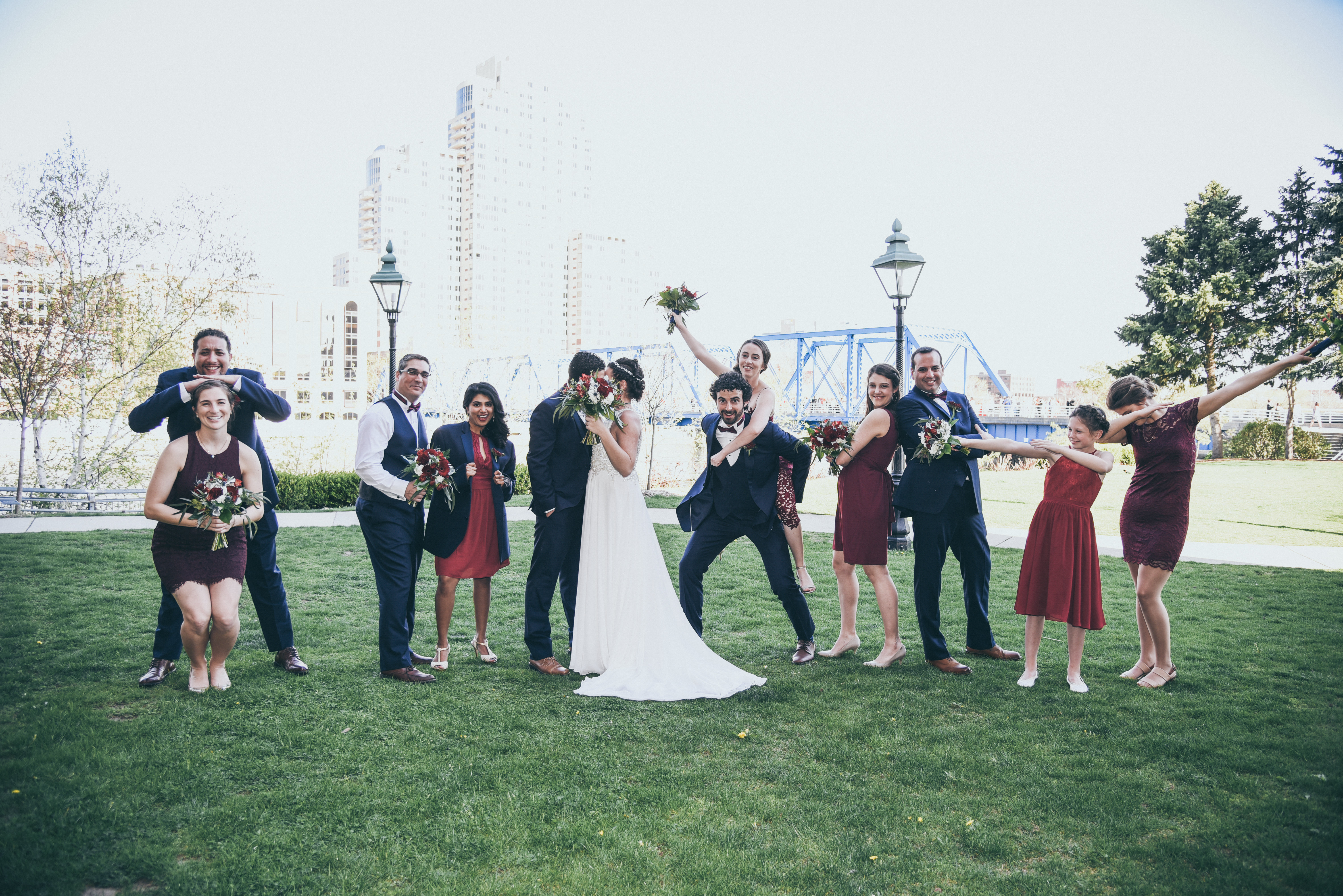 bridal party doing fun photos in front of a blue bridge in grand rapids michigan