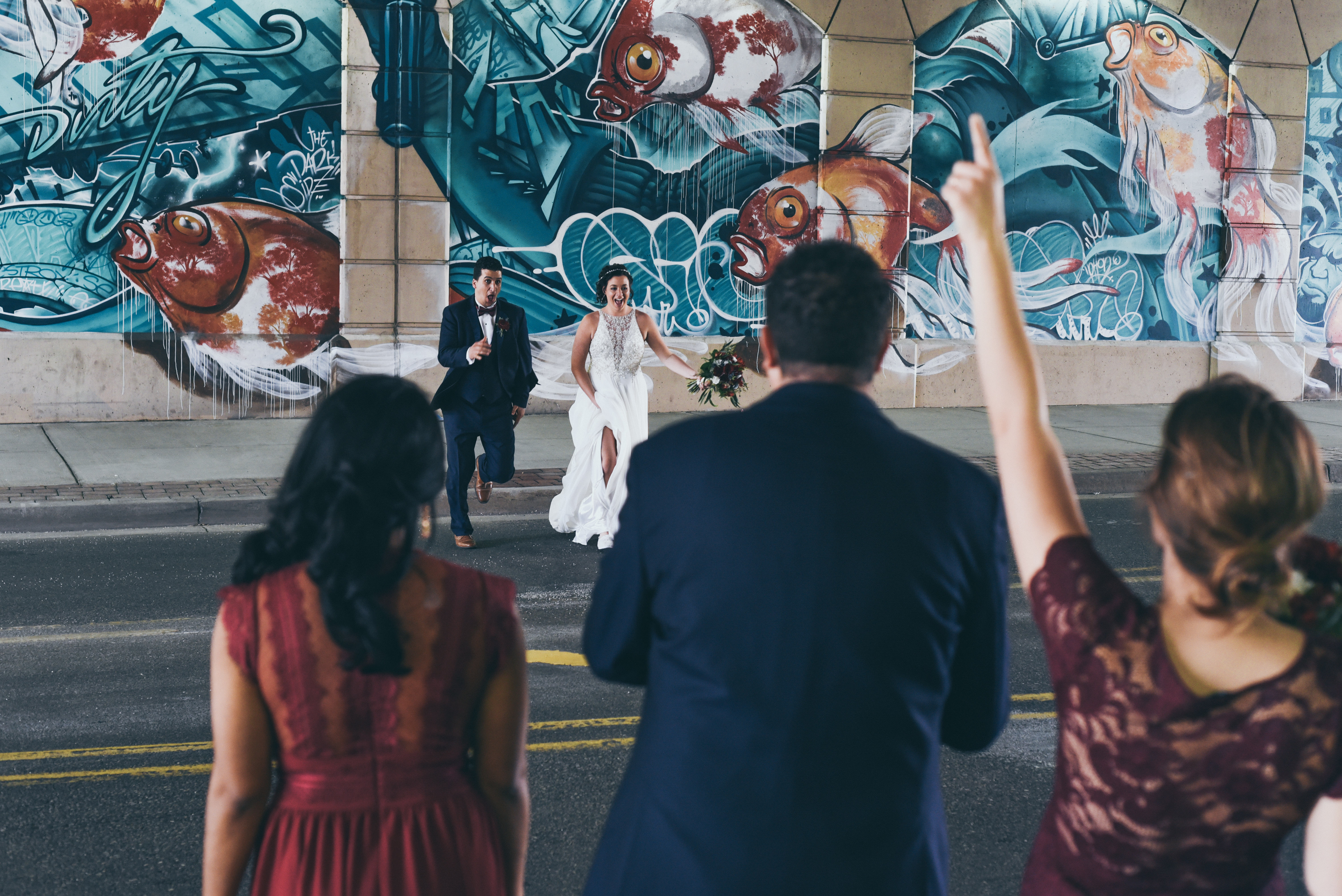 bride and groom in front of a mural in grand rapids michigan