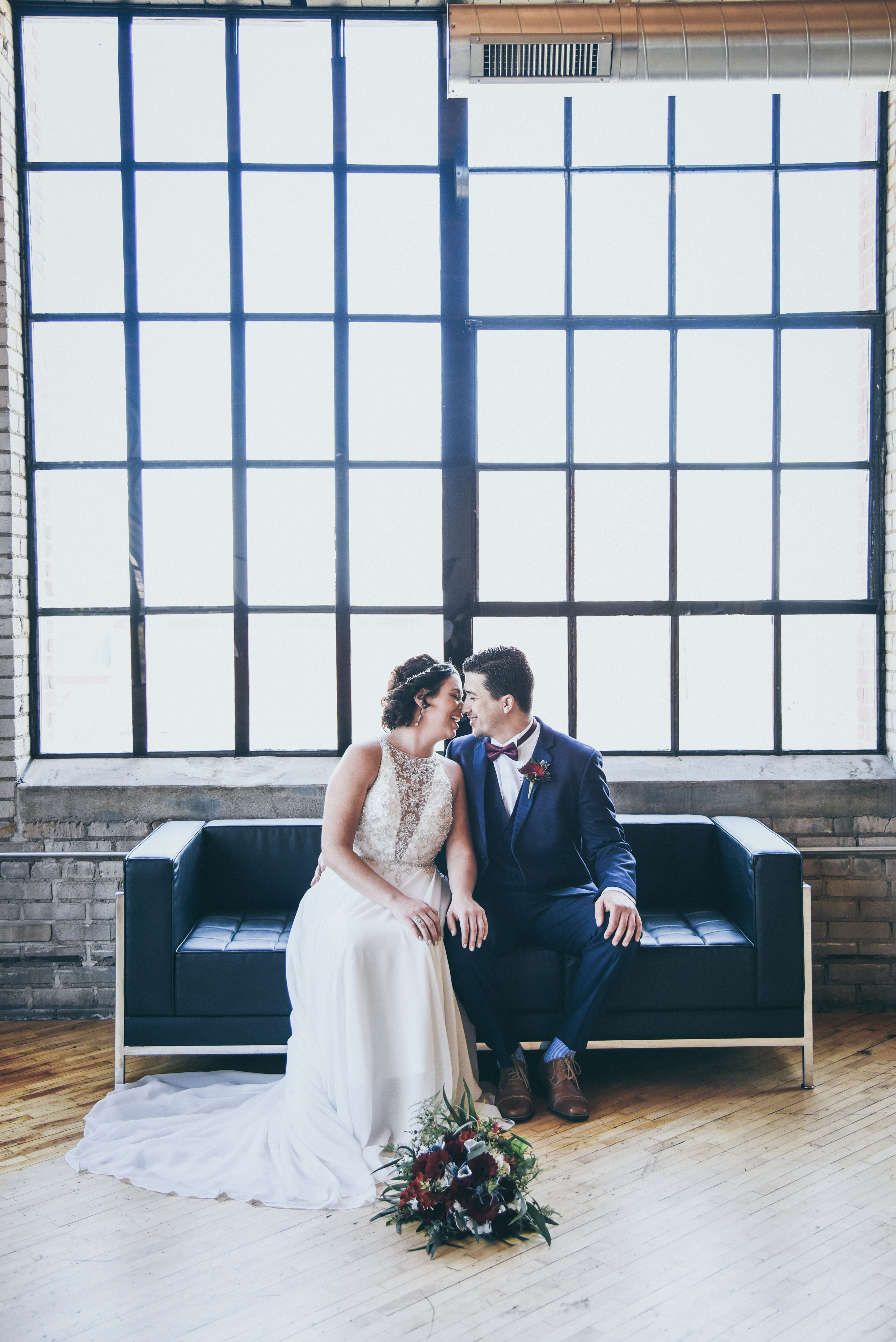 Bride and Groom together in an industrial loft venue on a black couch