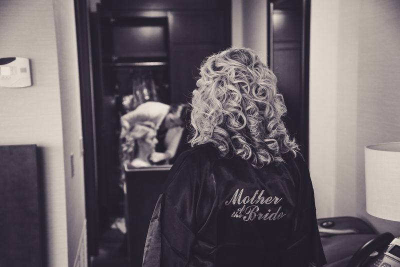black and white photo of mother of the bride looking at her daughter while she gets ready