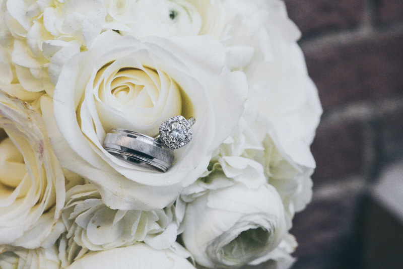 beautiful white wedding bouquet with wedding rings on a flower