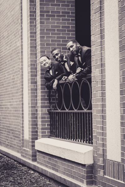 image of groom and groomsmen by an iron railing