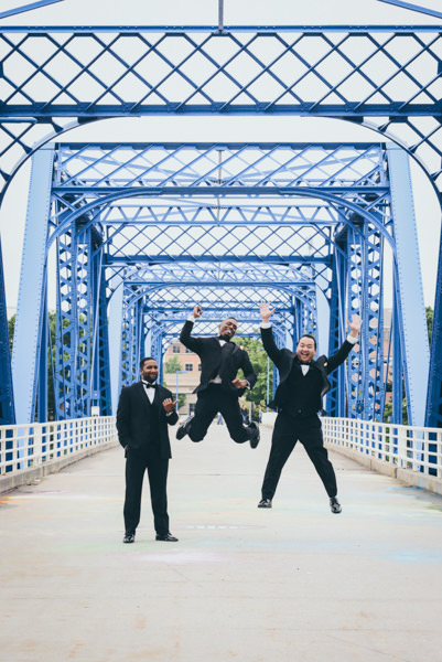 Groom and groomsmen jumping on a historic blue bridge