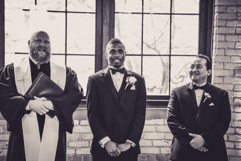 groom seeing his bride for the first time as groomsman looks on with a smile