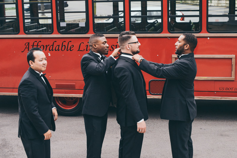 guys fixing a bowtie in front of a historic red trolley