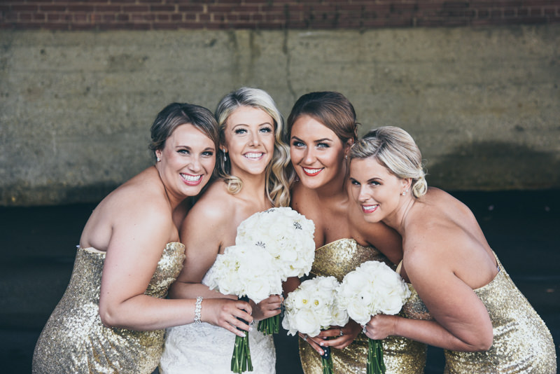 bride with bridesmaids in gold gowns with white bouquets