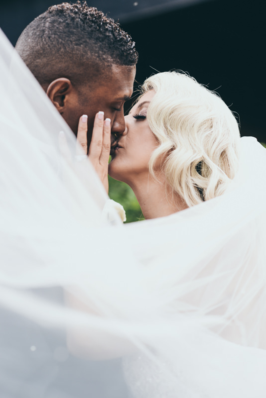 bride holding groom's face as she kisses him beneath a veil
