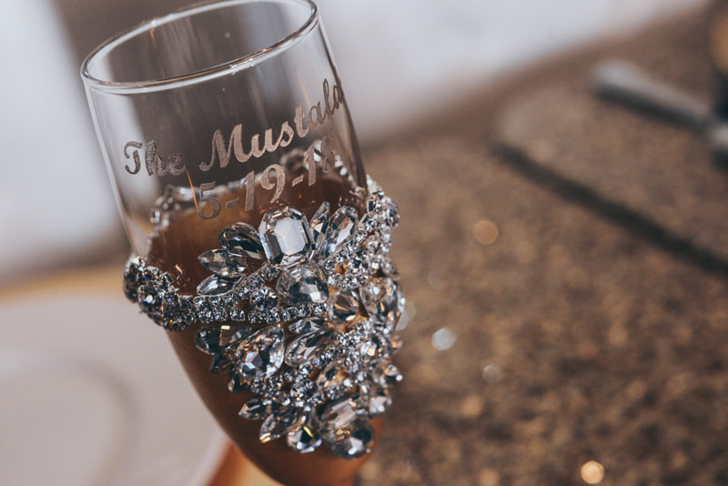 bejeweled and golden champagne flutes at a wedding reception
