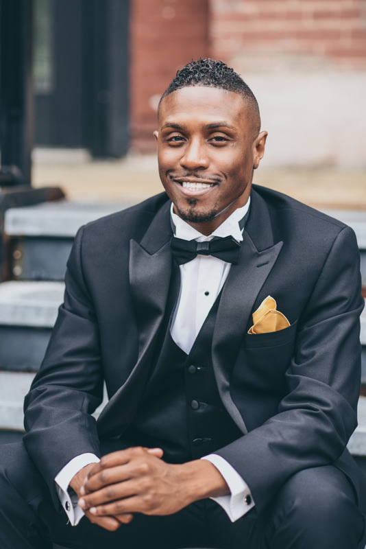 close up image of a groom sitting on stairs in a black tuxedo