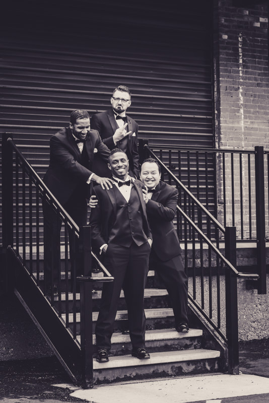 black and white funny photo of groom and groomsmen messing around on a set of stairs