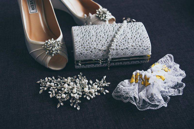 Bridal shoes, purse, jewelry and garter on a dark background