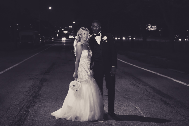 black and white image of bride and groom backlit and on a city street