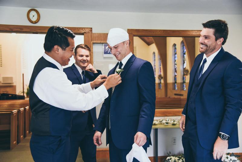 groomsman helping to pin flower on groom in church