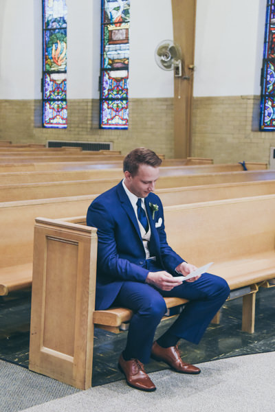 black and white photo of a groom sitting in a pew in church reading a letter from his bride