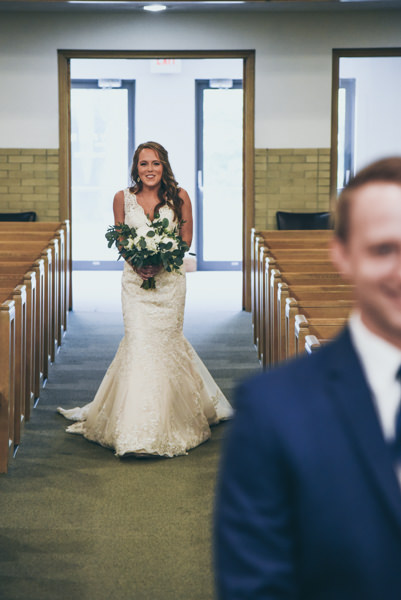 image of a bride walking up behind the groom in church during their first look