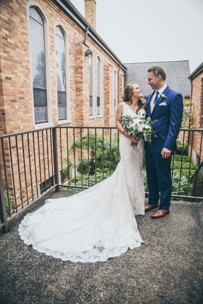 bride and groom standing near an iron fence