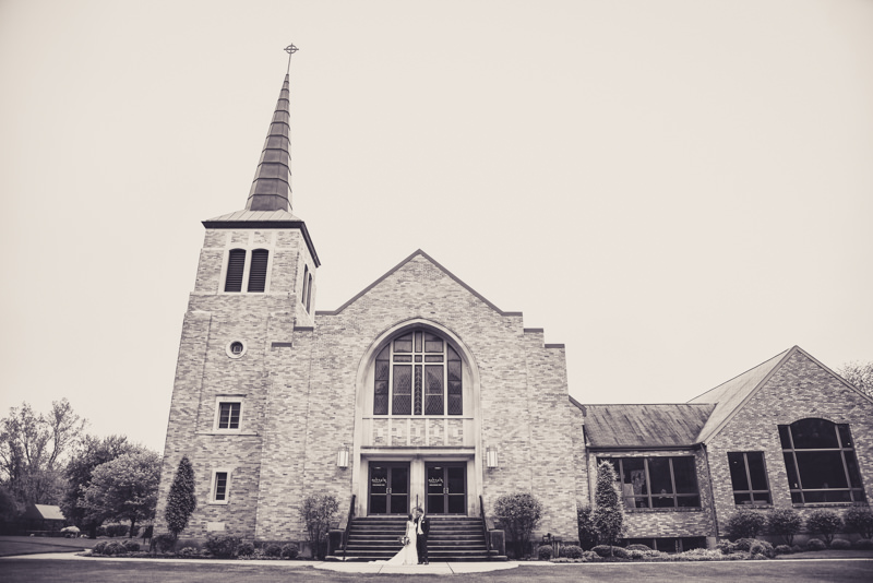 black and white image of a bride and groom in front of a church with a large spire