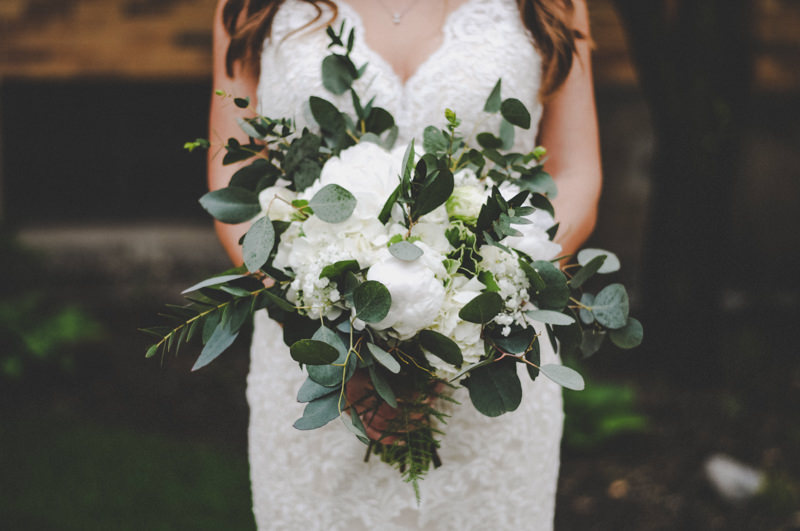 bride holding beautiful bouquet of white hydrangeas and greenery