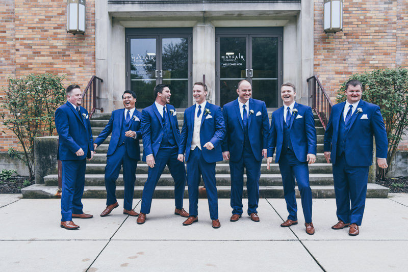 groomsmen laughing in front of the church
