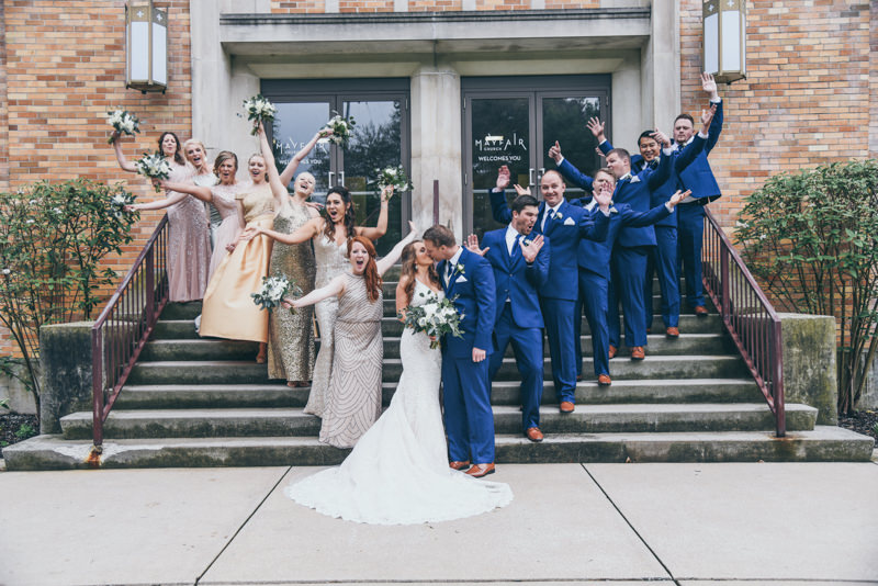 bridal party having fun on the steps in front of the church