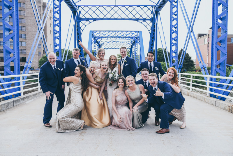 bride and groom with bridal party around them on a blue bridge