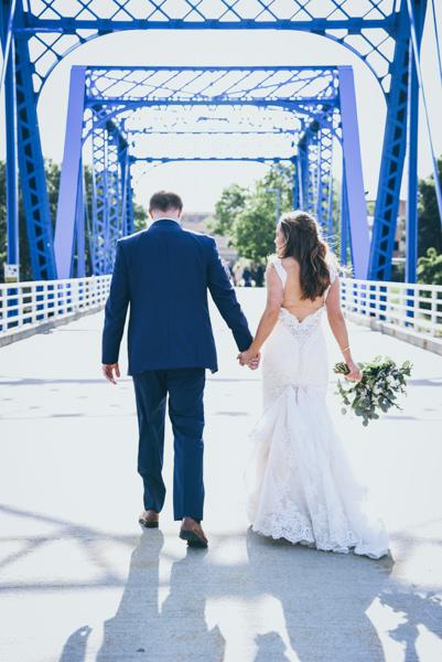 bride and groom walking away on a blue bridge