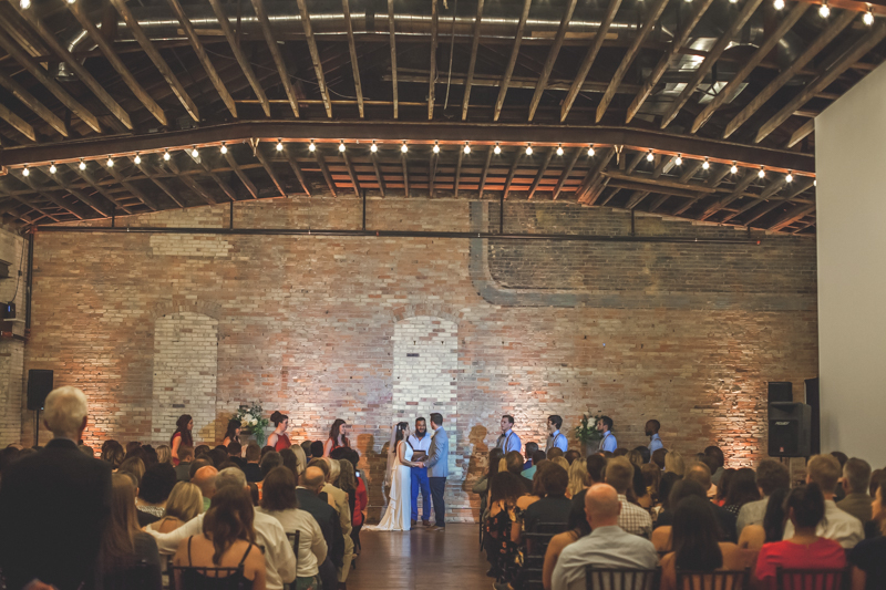 wide photo of wedding ceremony in an old brick building