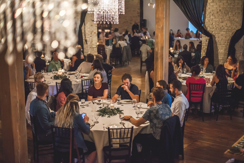 guests eating dinner at a wedding reception in an old vintage brick building with crystal chandeliers