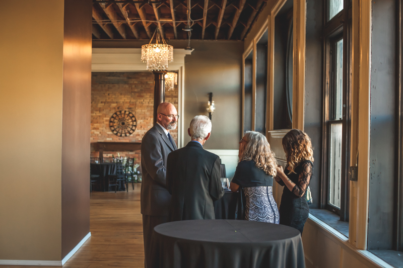 guests enjoying cocktail hour near old windows and crystal chandeliers at a wedding reception