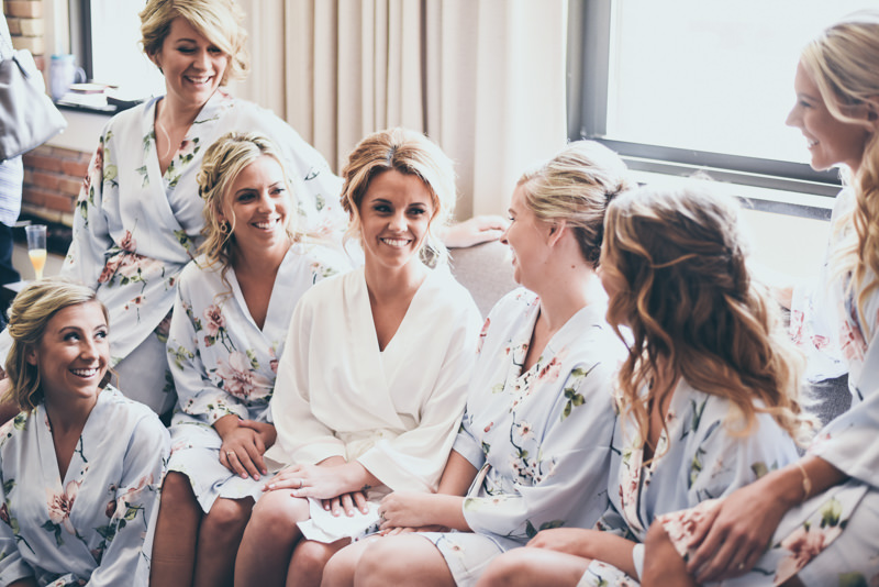 bride sitting with bridesmaids as she gets ready for her wedding