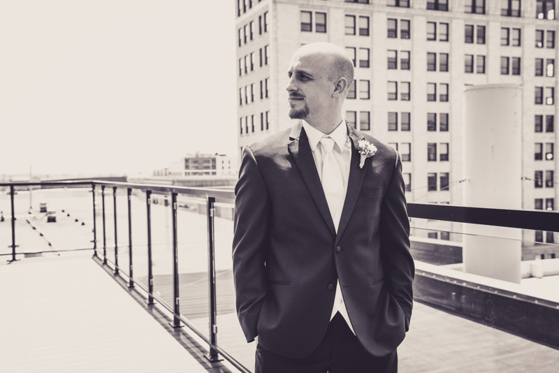 black and white image of a groom on the roof of a city building
