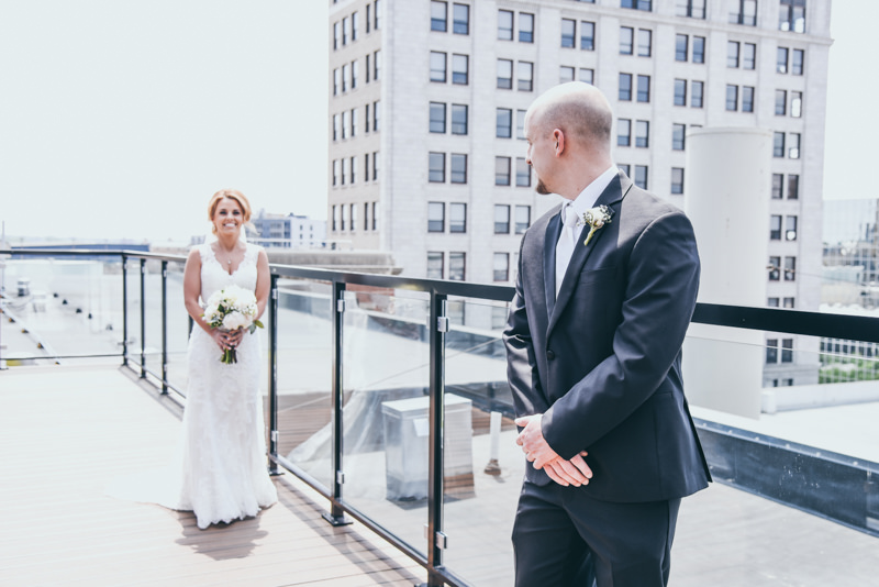 a groom on the roof of a city building turning to see his bride for the first time