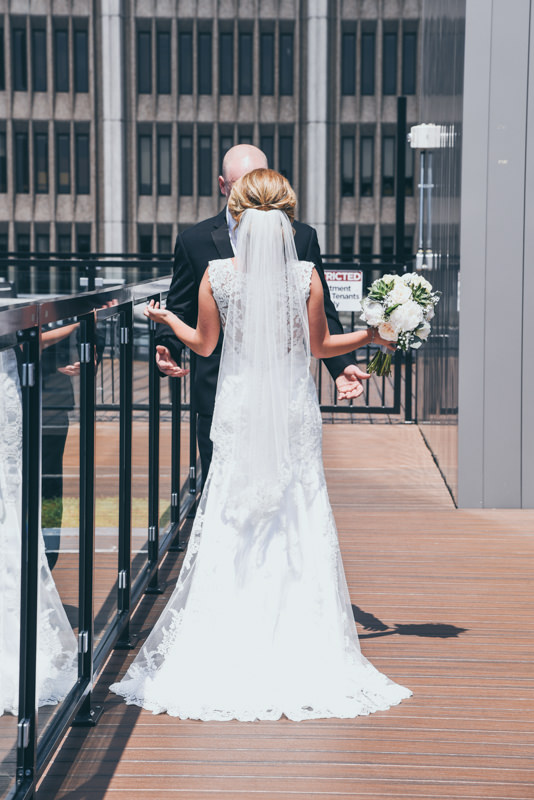 bride and groom on a city building roof facing each other