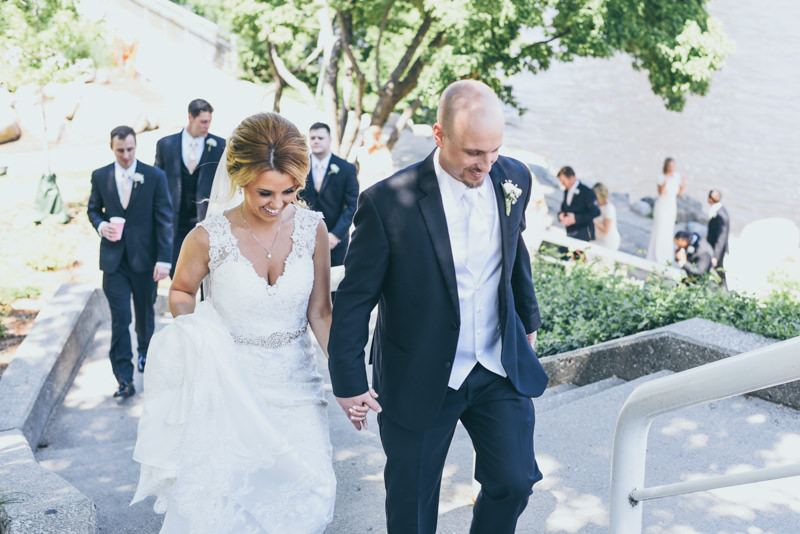 bride and groom walking up outdoor stairs while bridal party follows