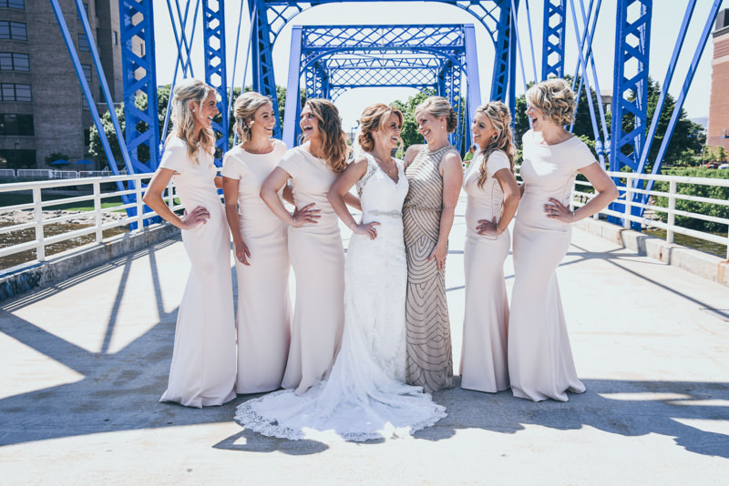 bride and bridesmaids laughing together on a blue bridge