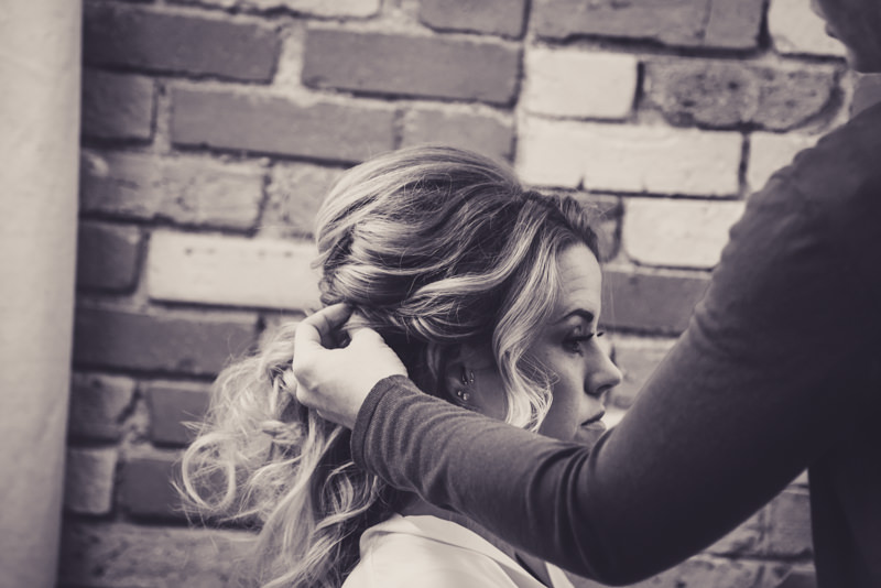 black and white image of a bride getting her hair done in front of a brick wall