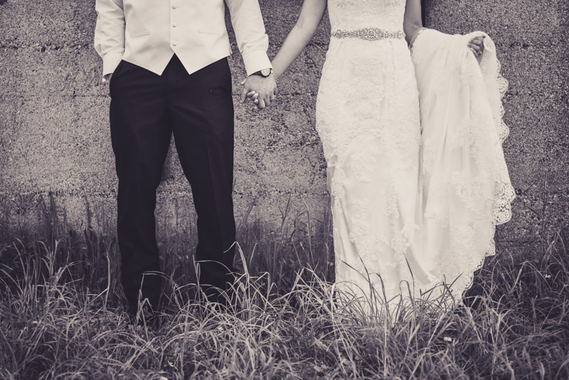black and white image of the lower halves of a bride and groom holding hands in front of an old warehouse