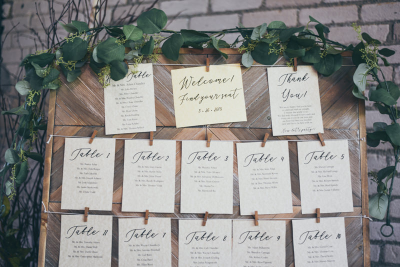 wooden wedding place setting display with greenery
