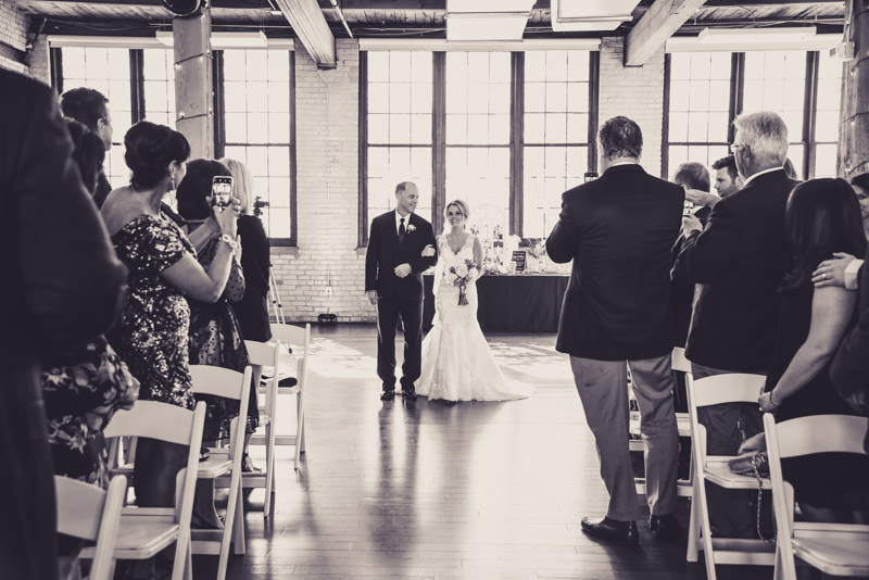 black and white image of a father walking his daughter down the aisle