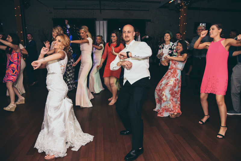 bride and groom having fun dancing at wedding reception