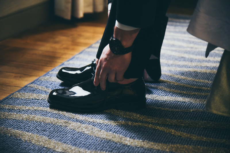 groom adjusting his shoes in a hotel room before his wedding