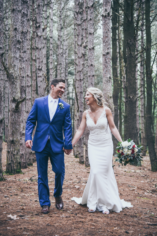 bride and groom laughing and walking in a pine forest