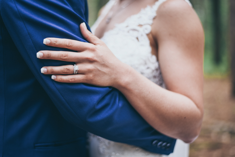 close up of a brides hands as she holds her groom in a pine forest