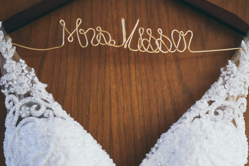 photo of a wire hanger spelling a brides name and holding a lace wedding gown