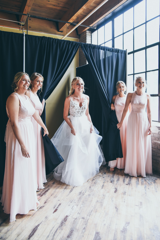 bridesmaids pulling back curtains to reveal the bride to her father for the first time