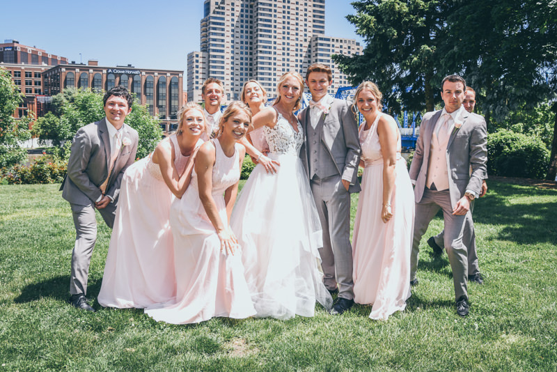 Bridal party having fun on a lawn with a city skyline behind them
