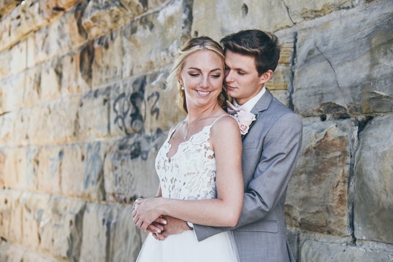 bride and groom holding each other, faces touching, against a stone wall